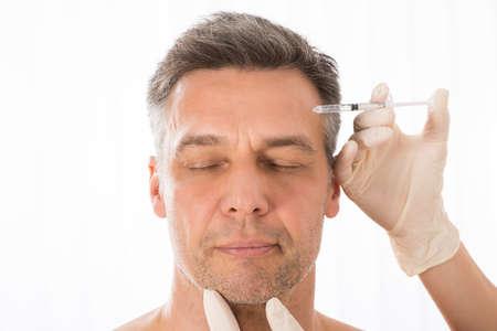 Photo pour Close-up Of Mature Man Get Injection On His Face - image libre de droit