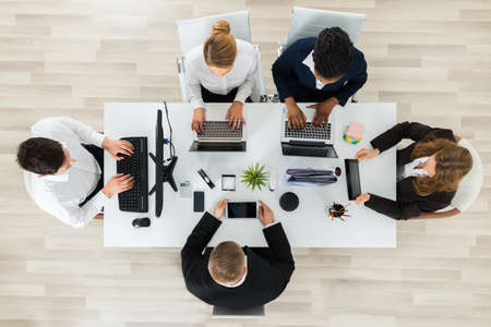 High Angle View Of Businesspeople Working On Computers And Laptops In Office