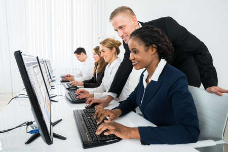 Photo pour Young Happy Manager Assisting His Female Staff In Office - image libre de droit