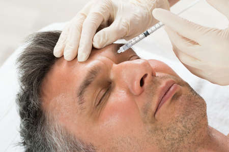 Photo pour Mature Man Receiving Cosmetic Injection With Syringe In Clinic - image libre de droit