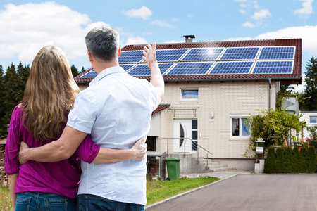Photo pour Rear View Of Couple Standing In Front Of Their House - image libre de droit