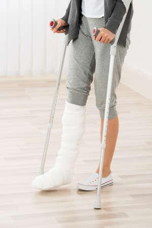 Photo pour Close-up Of Woman Leg In Plaster Cast Using Crutches While Walking - image libre de droit