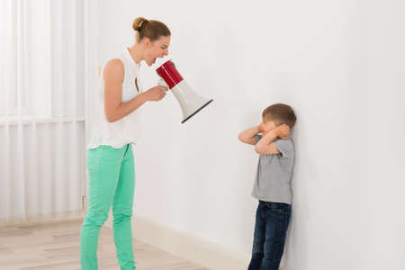 Photo for Mother Screaming At Her Son Through Megaphone - Royalty Free Image