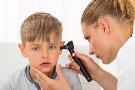 Foto für Close-up Of Female Doctor Examining Boy's Ear With An Otoscope - Lizenzfreies Bild