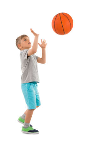 Foto de Photo Of Boy Throwing Basketball Over White Background - Imagen libre de derechos