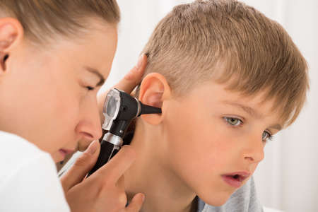Photo for Close-up Of Female Doctor Examining Boy's Ear With An Otoscope - Royalty Free Image