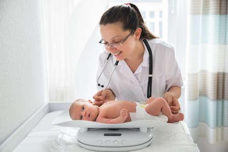Foto de Happy Female Pediatrician Checking Weight Of Cute Baby - Imagen libre de derechos