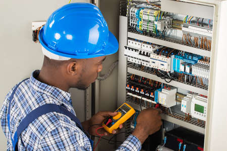 Photo for Young African Male Technician Examining Fusebox With Multimeter Probe - Royalty Free Image