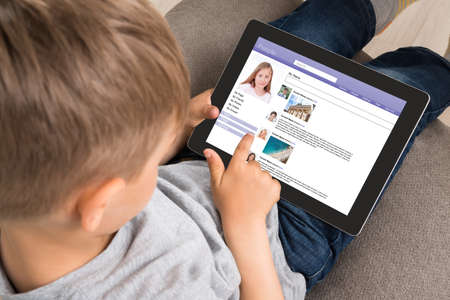 Photo for Close-up Of Cute Little Boy Using Social Networking Site On Digital Tablet At Home - Royalty Free Image