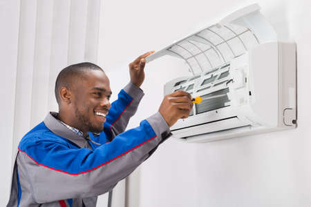 Photo for Happy Young African Male Technician Repairing Air Conditioner - Royalty Free Image