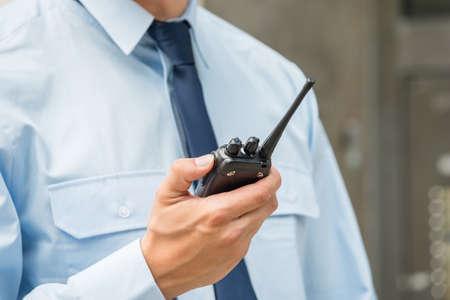 Foto de Close-up Photo Of Security Guard Holding Walkie-talkie - Imagen libre de derechos