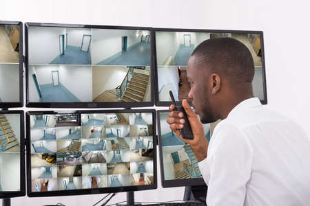 Photo pour Male Operator Talking On Walkie-Talkie While Looking At CCTV Footage - image libre de droit