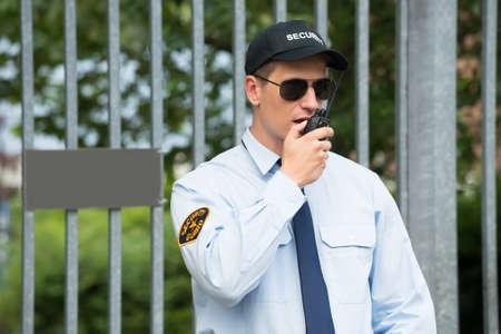 Photo pour Close-up Of Male Security Guard Talking On Walkie-talkie - image libre de droit