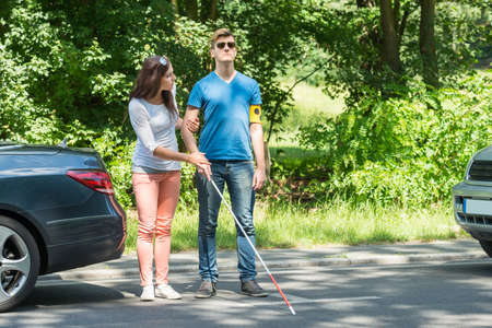 Photo pour Young Woman Helping Blind Man Wearing Armband On Street - image libre de droit