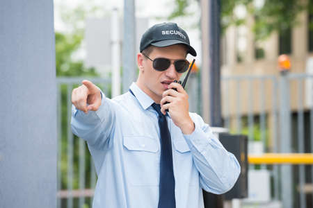 Young Male Security Guard Gesturing While Using Walkie-talkie