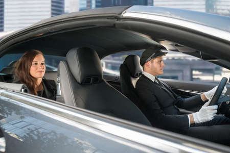 Photo pour Beautiful Young Woman Traveling In A Car With Male Handsome Chauffeur - image libre de droit