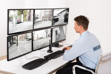 Photo pour Rear View Of A Young Male Security Guard Monitoring Multiple CCTV Footage - image libre de droit