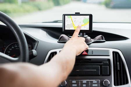 Photo pour Close-up Of Female's Hand Using GPS Navigation Inside Car - image libre de droit