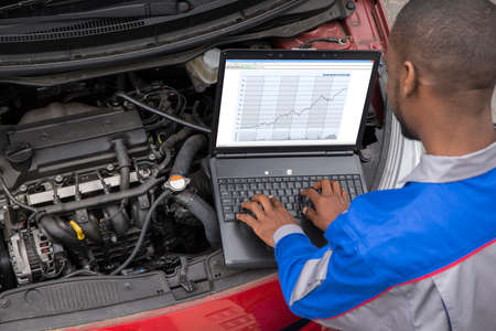 Photo for Young Male Mechanic Using Laptop While Examining Car Engine - Royalty Free Image