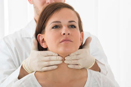Photo pour A Doctor Performing Physical Exam Palpation Of The Thyroid Gland - image libre de droit