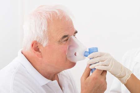 Photo pour Close-up Of Senior Man Using Oxygen Mask In Clinic - image libre de droit