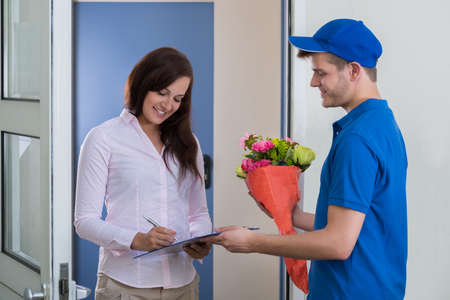 Photo for A Young Woman Signs For Receipt Of A Bouquet Of Flowers - Royalty Free Image