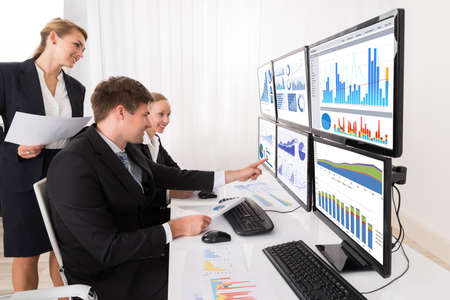 Photo pour Happy Young Businesspeople Analyzing Graphs On Multiple Computers In Office - image libre de droit