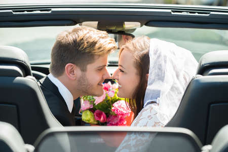 Photo pour Newlyweds Young Smiling Couple Kissing In The Wedding Car - image libre de droit