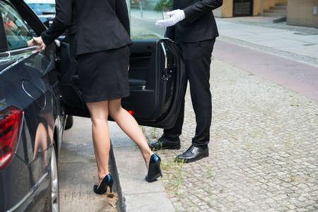 Photo pour Male Chauffeur Opening The Car Door For The Businesswoman On Street - image libre de droit
