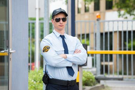 Photo pour Confident Young Male Security Guard Standing Arm Crossed - image libre de droit