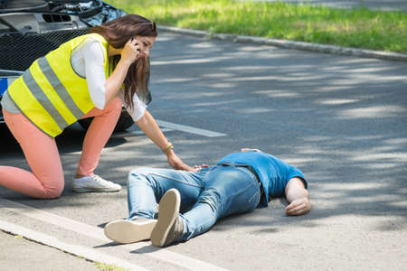 Photo for Woman Calling For Emergency Help Looking At Injured Man After Accident - Royalty Free Image