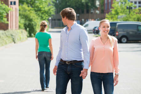 Photo pour Young Man Walking With His Girlfriend On Street Looking At Another Woman - image libre de droit