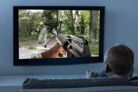 Foto de Boy Sitting On Sofa Playing Action Game On Television - Imagen libre de derechos