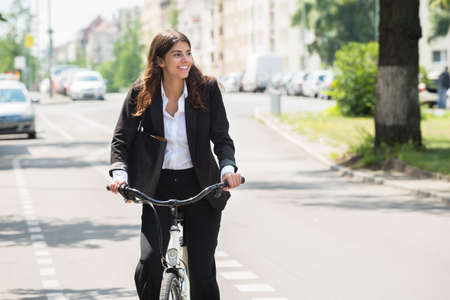Photo Of Happy Young Businesswoman Commuting On Bicycle