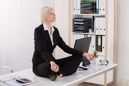 Young Businesswoman Doing Yoga On Desk In Office