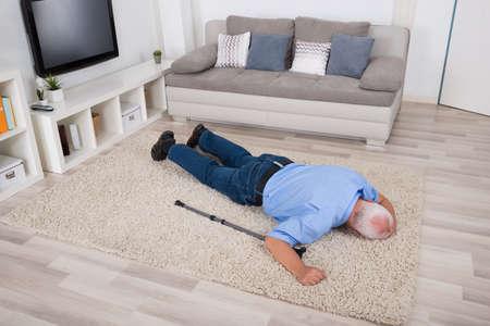 Photo pour Unconscious Disabled Senior Man Lying On Carpet At Home - image libre de droit