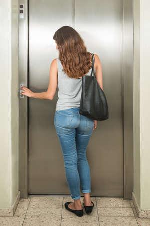 Photo pour Rear View Of A Young Woman With Handbag Using Elevator - image libre de droit
