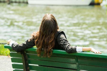 Foto de Rear View Of A Businesswoman Sitting On Bench - Imagen libre de derechos