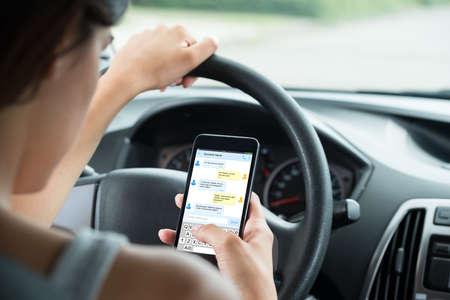 Photo pour Close-up Of Woman Sitting Inside Car Typing Text Message On Mobile Phone - image libre de droit