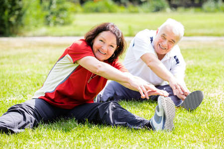 Foto per Smiling Senior Couple Doing Fitness Exercise In Park - Immagine Royalty Free