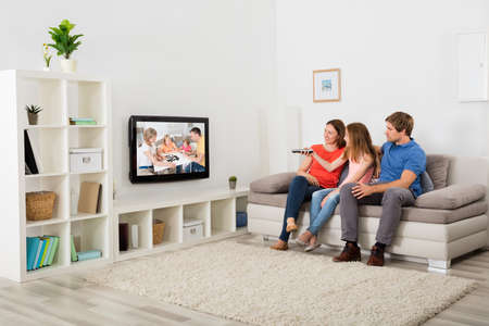 Photo pour Family Sitting On Sofa Watching Television At Home - image libre de droit