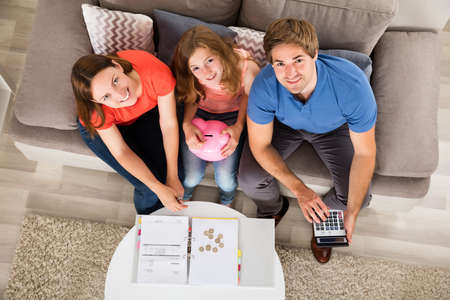 Photo pour High Angle View Of A Smiling Family Calculating Tax - image libre de droit