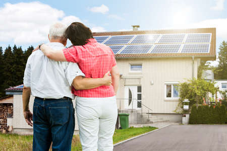 Photo for Rear View Of Senior Couple Standing In Front Of Their House - Royalty Free Image