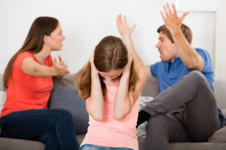 Foto de Upset Girl Covering Her Ears In Front Of Parent Having Argument - Imagen libre de derechos