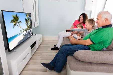 Grandparents And Kids Watching Television On Couch Together At Home