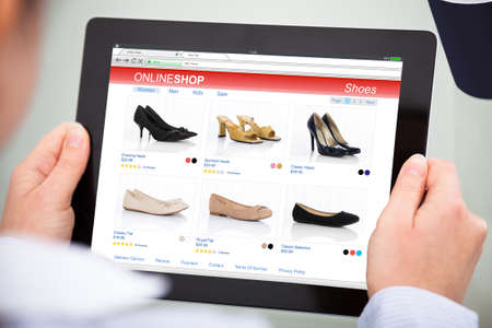 Photo pour Close-up Of Person Purchasing Footwear While Doing Online Shopping On Digital Tablet - image libre de droit