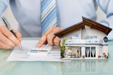 Photo pour Businessman Calculating Expanses Using Calculator With House Model On Office Desk - image libre de droit