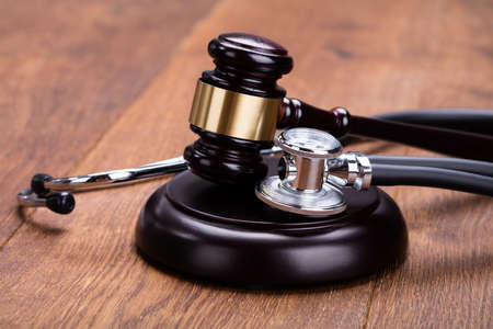 Close-up Of Gavel With Medical Stethoscope On Wooden Desk In Courtroom