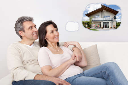 Photo pour Mature Happy Couple Relaxing On Sofa Dreaming Of Having Their Own House Together - image libre de droit