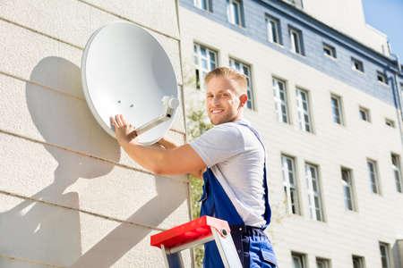 Photo pour Young Man Fitting TV Satellite Dish To Wall - image libre de droit